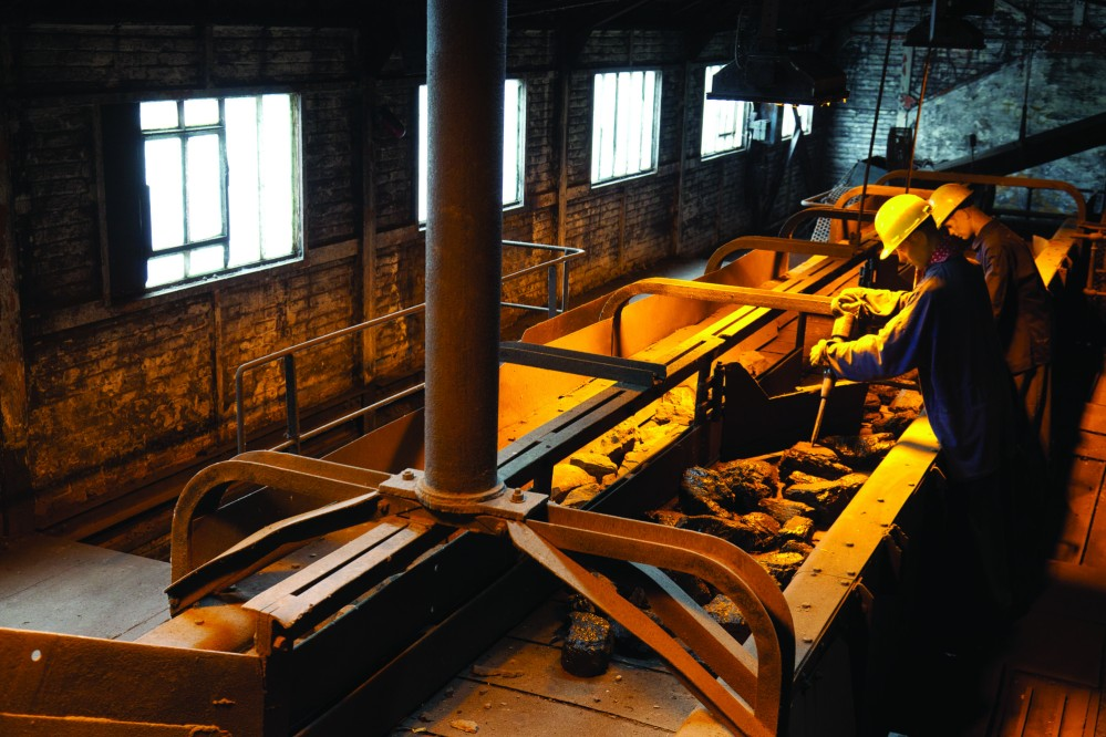 Workers use hammers to crush coal into smaller pieces in the sorting plant. – © FTPL