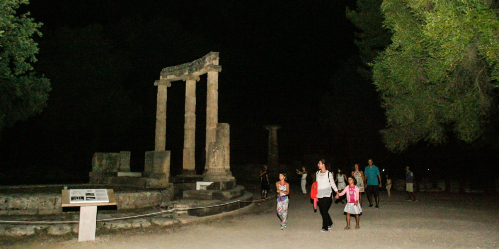 Visitors passing by the Philippeion as they enjoy a night stroll in the archaeological site of Olympia. – © Giannis Spyrounis / www.ilialive.gr