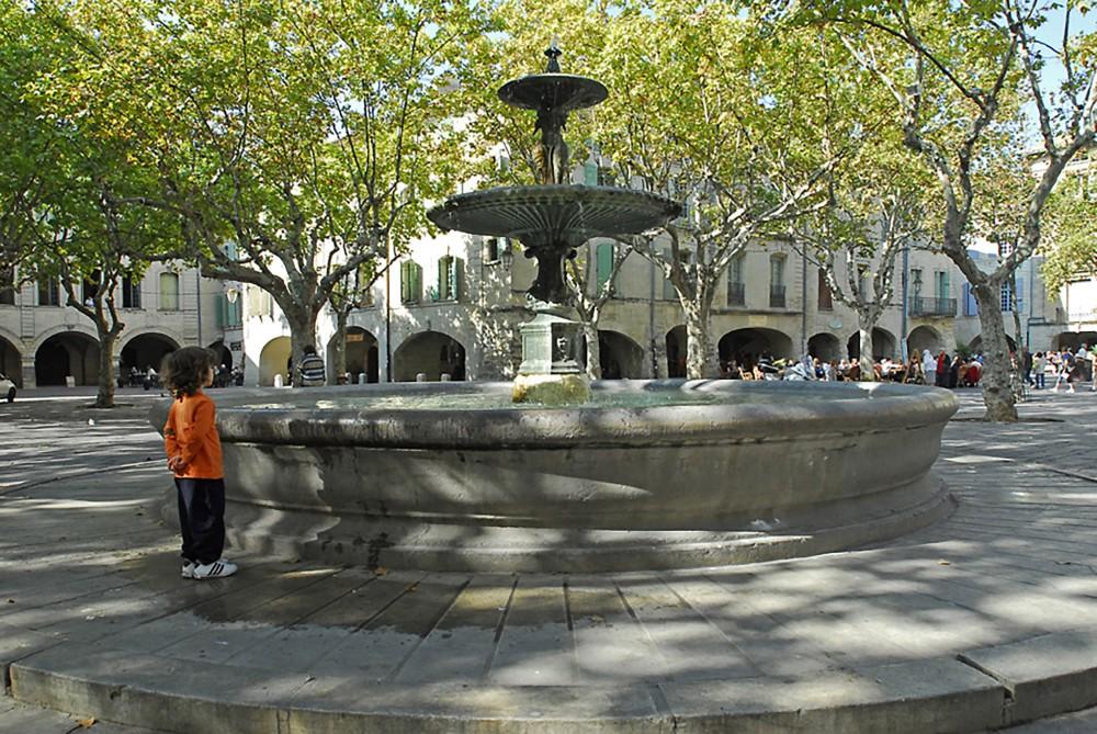 Place aux Herbes with central fountain, installed in 1855. – © Aline Périer / Uzès Tourist Office