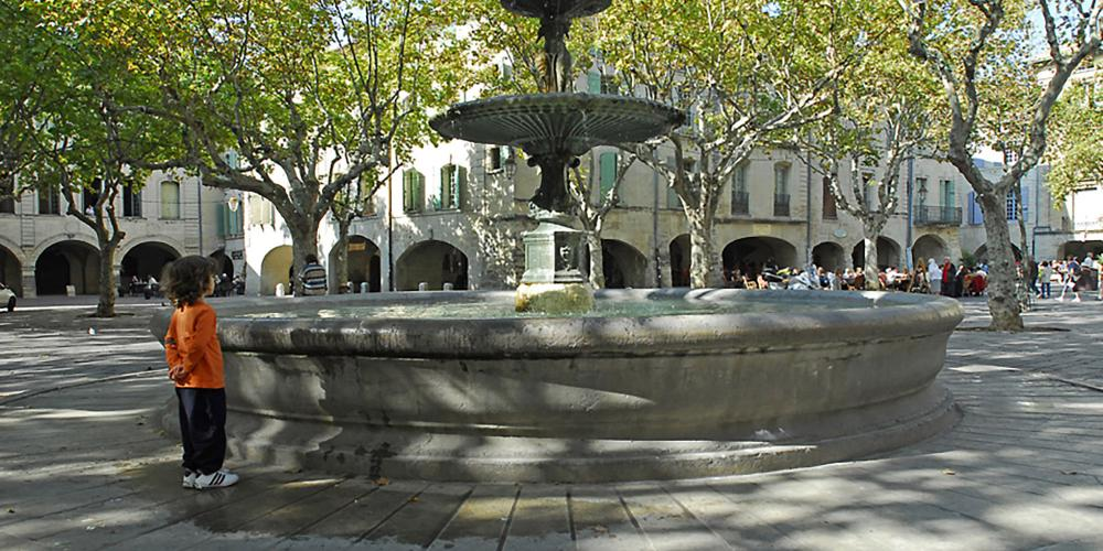 Place aux Herbes with central fountain, installed in 1855. – © Aline Périer / Uzès Tourist Office