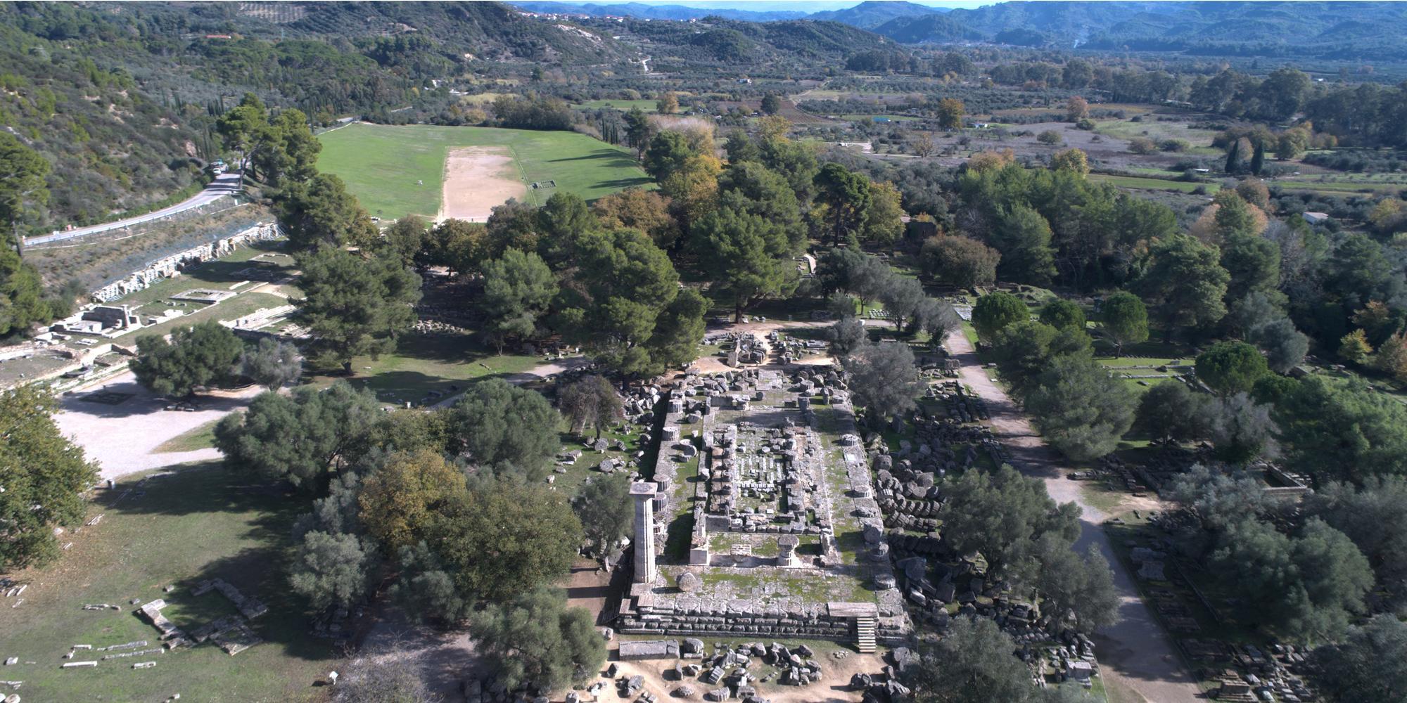 Vue du site d'Olympie avec le temple de Zeus au premier plan et le stade à l'arrière-plan. - © Ministère Hellénique de la Culture et des Sports / Ephorat des Antiquités d'Ilia