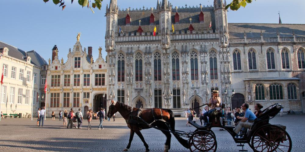 Take in Burg Square at a relaxed speed with a horse-drawn carriage tour. – © Jan D'Hondt / VisitBruges