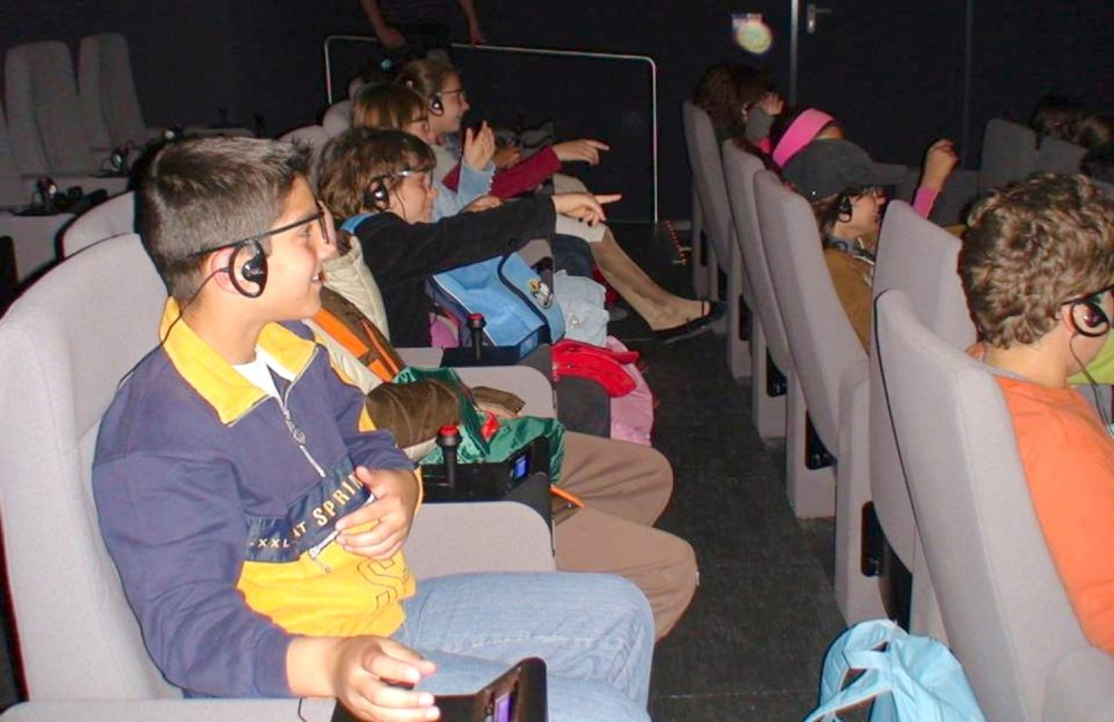 Kids enjoying a dramatised virtual tour in the Sanctuary of Zeus at the 3D Interactive Theatre – © Hellenic Ministry of Culture and Sports / Ephorate of Antiquities of Ilia