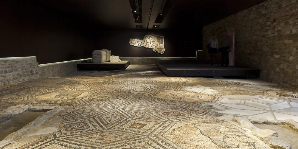 The mosaic floor in the Südhalle and, on the wall in the background, the mosaic with the peacock, a symbol of immortality and an allegory of resurrection. – © Gianluca Baronchelli