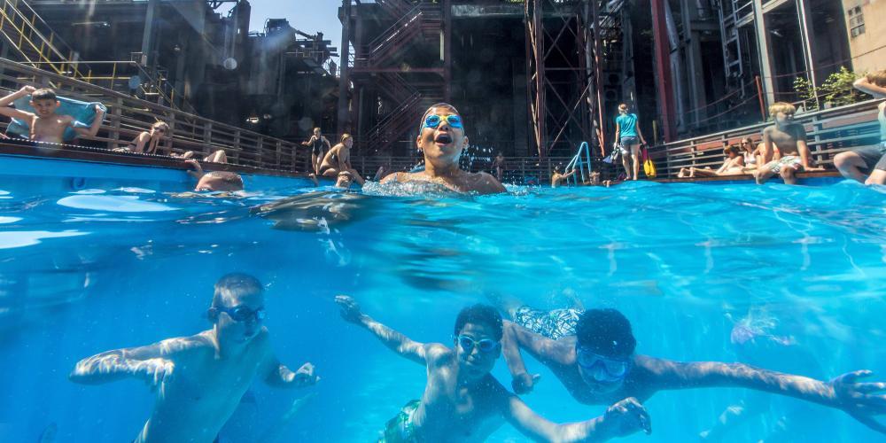 Pendant les vacances d'été en Rhénanie du Nord-Westphalie, cette piscine est un lieu de rencontre populaire pour les enfants et les adolescents des quartiers voisins et un symbole du changement structurel dans la région de la Ruhr. – © Jochen Tack / Zollverein Foundation