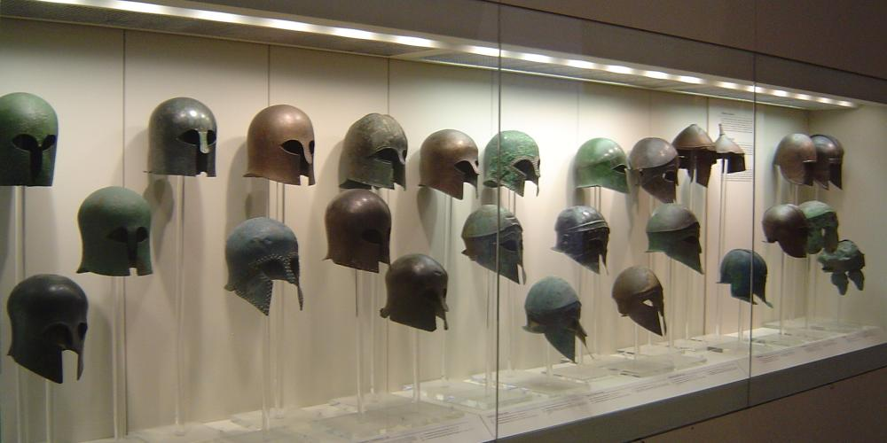 The range of valuable finds includes a display case with a collection of finely preserved bronze helmets of the Archaic-Classical periods. – © Hellenic Ministry of Culture and Sports / Ephorate of Antiquities of Ilia