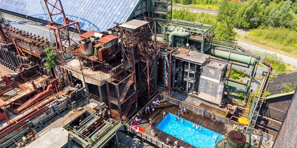 Pause baignade dans la piscine bleue au milieu de l'ancienne cokerie : lorsque la météo est au beau fixe, vous pouvez vous rafraîchir, prendre un bain de soleil et vous détendre à la piscine tous les jours de 12h00 à 20h00 pendant les vacances d'été en Rhénanie-du-Nord-Westphalie. – © Jochen Tack / Zollverein Foundation