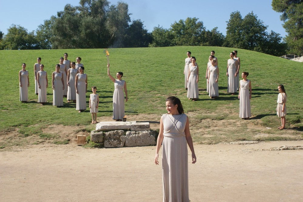 The head priestess raises the Olympic Flame moments before the torch relay begins in the Stadium. – © Hellenic Ministry of Culture and Sports / Ephorate of Antiquities of Ilia