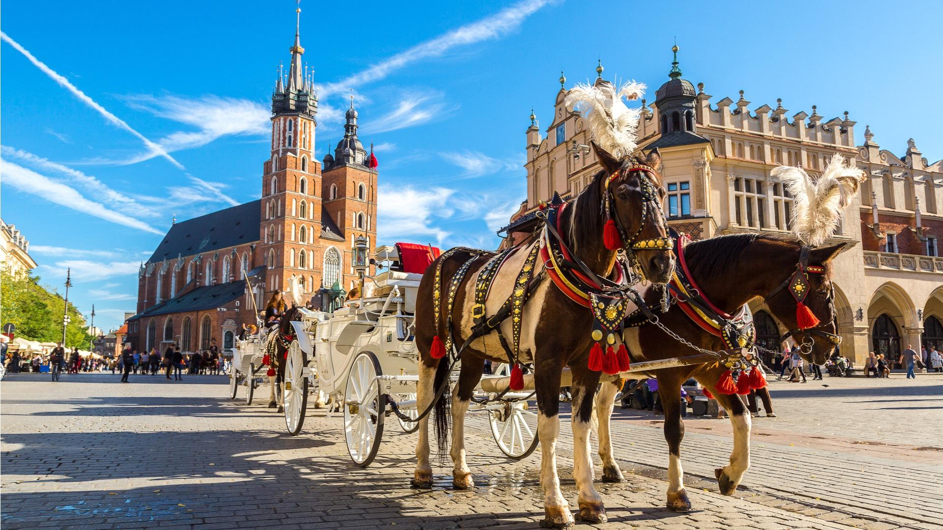 A carriage ride around the Old Town is a romantic way to tour the city, particularly in the evening, when the whole Square, and especially St. Mary's Basilica and the Cloth Hall are splendidly illuminated. – © S-F / Shutterstock