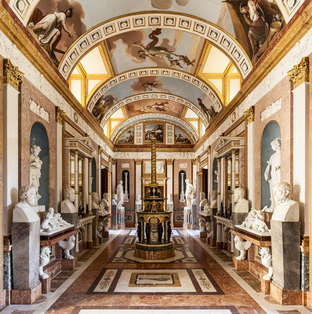 "The statue gallery features the busts of Greek sages and philosophers. On the floor there are some Roman mosaics from Merida. In the centre of the room is a unique clock known as ""Trajan's Column"" made in Paris in 1804. – © Patrimonio Nacional"