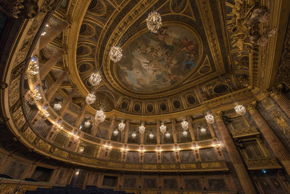 L'Opéra Royal est l'une des plus grandes œuvres de l'architecte Ange-Jacques Gabriel. Inaugurée en 1770 sous le règne de Louis XV, elle était alors la plus grande salle de concert d'Europe et représentait une prouesse en termes techniques aussi bien que'en termes de raffinement de la décoration. Le lieu a accueilli des célébrations, des spectacles et des débats parlementaires. – © Thomas Garnier