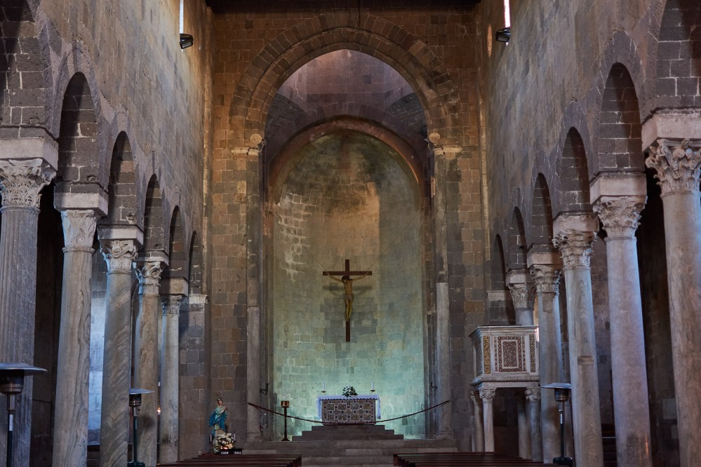 Central nave of the Romanesque Cathedral with the colonnade and the apse area. – © Emma Taricco
