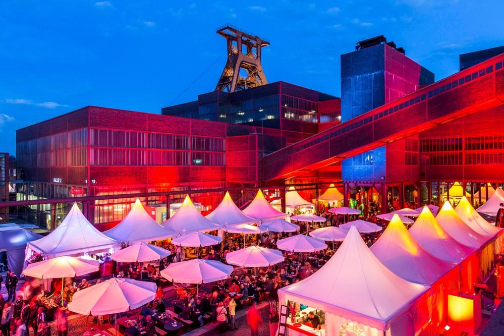 En été, de nombreux événements en plein air ont lieu à Zollverein. Un des plus populaires est organisé en août : le Gourmetmeile Ruhr, un festival gastronomique où de nombreux chefs d'Essen présentent leurs talents et leurs spécialités régionales. – © Jochen Tack / Zollverein Foundation