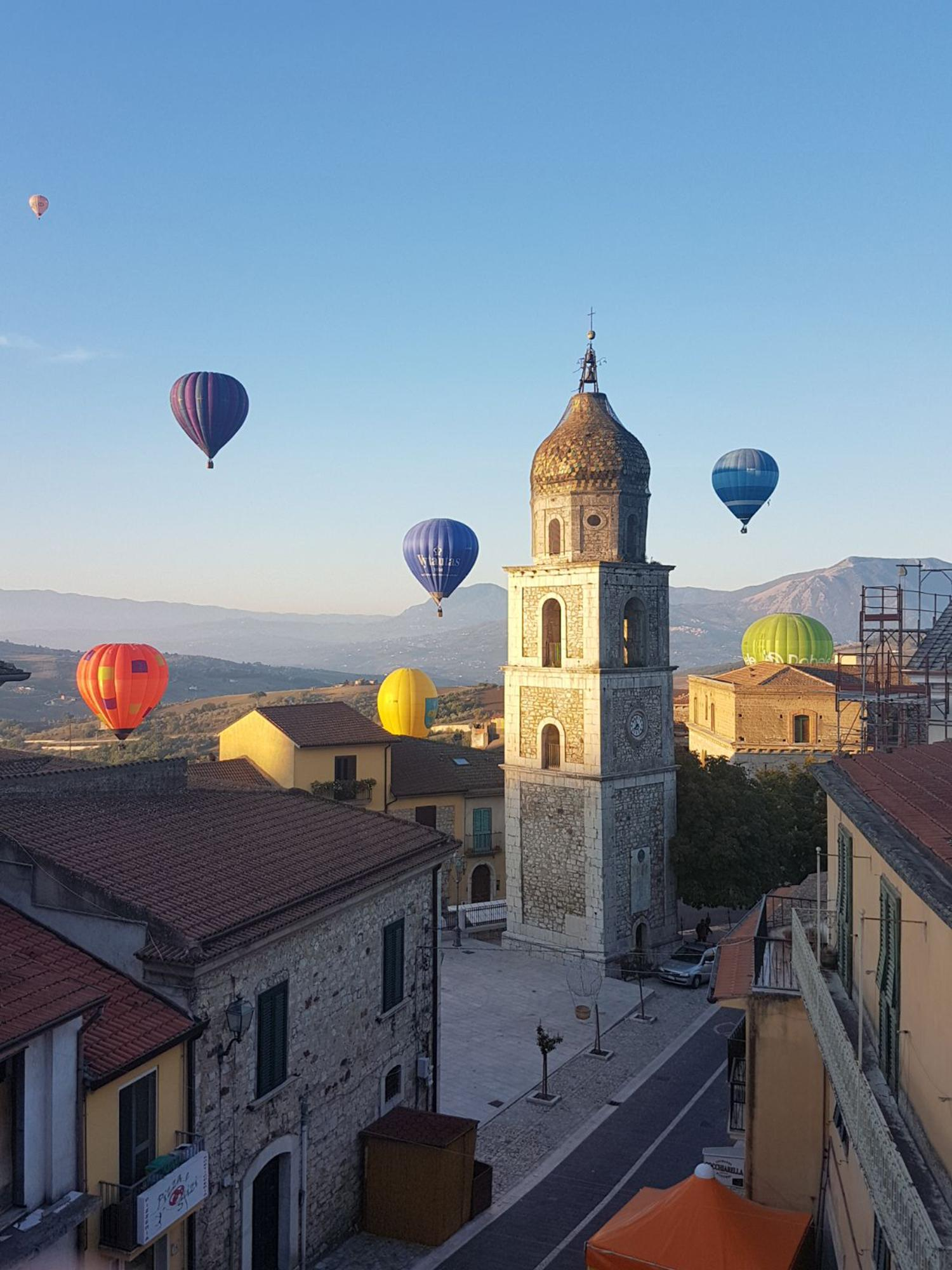 Balloons in flight over the churchyard of St. Nicholas and St. Rocco with the bell tower. – © Archivio Balooning Festival