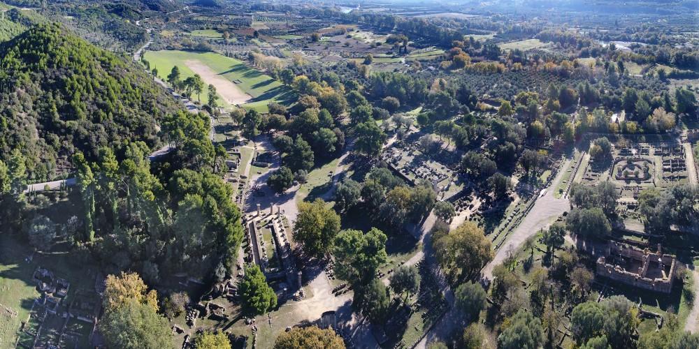 Vue du site d'Olympie avec les temples d'Héra et de Zeus au premier plan et le stade en arrière-plan. – © Ministère Hellénique de la Culture et des Sports / Ephorie des Antiquités d'Ilia (efailias)