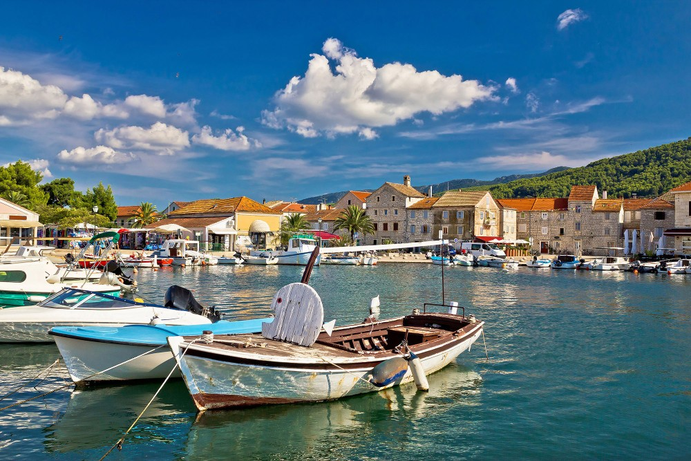 The old town of Stari Grad sits around a harbour where local fishing boats are moored. – ©xbrchx / Shutterstock