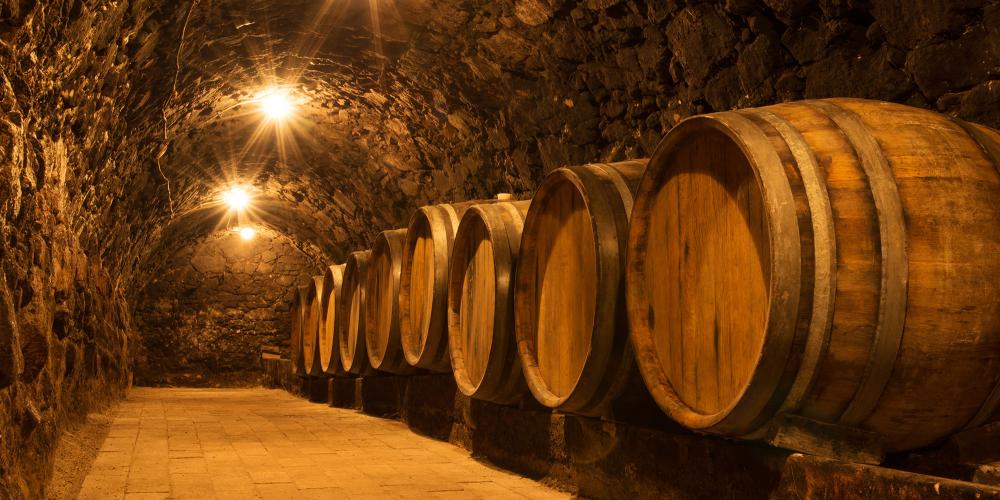 Stopping at the local wineries, visitors will taste the different dry and sweet styles and learn about their production—such as oak barrel storage like this in the tunnel of an old cellar. – © Natalia Bratslavsky / Shutterstock