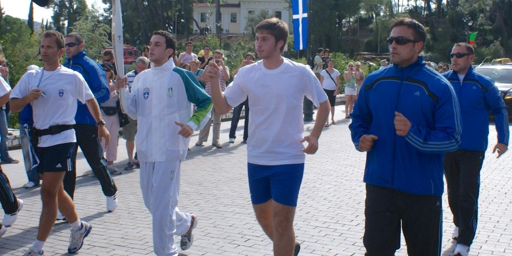 The group of runners carrying the Olympic Flame departs from the City of Olympia. The Museum of the History of the Olympic Games of Antiquity is visible in the background. – © Hellenic Ministry of Culture and Sports / Ephorate of Antiquities of Ilia