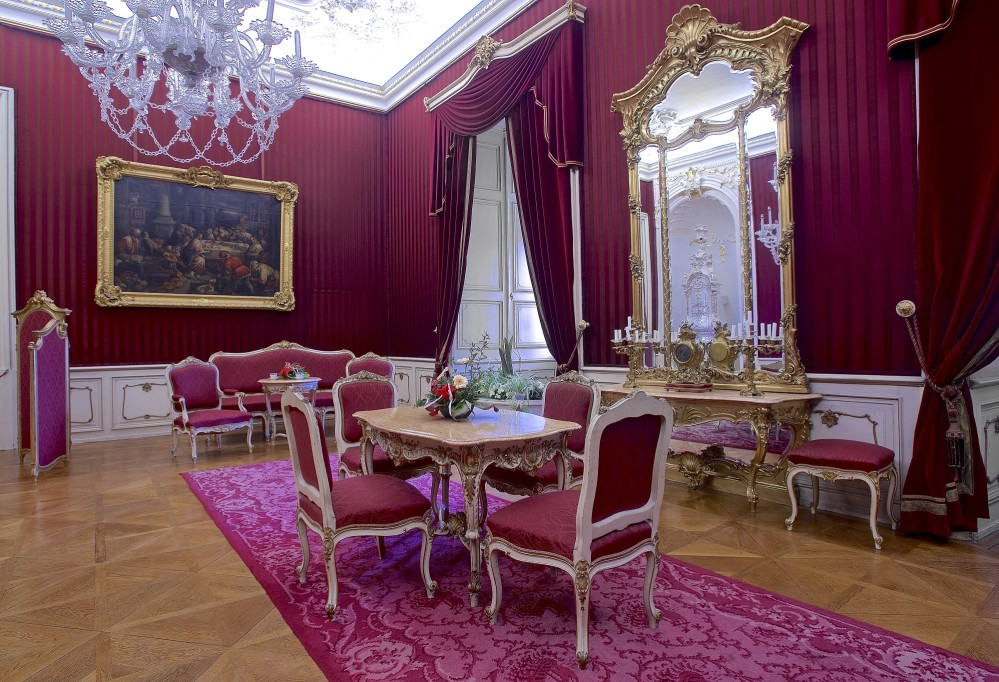 The Pink Room is equipped with richly decorated furniture and paintings. The crystal chandelier and Venetian mirror demonstrate the skill of Czech and Italian craftsmen. – © Tomas Vrtal