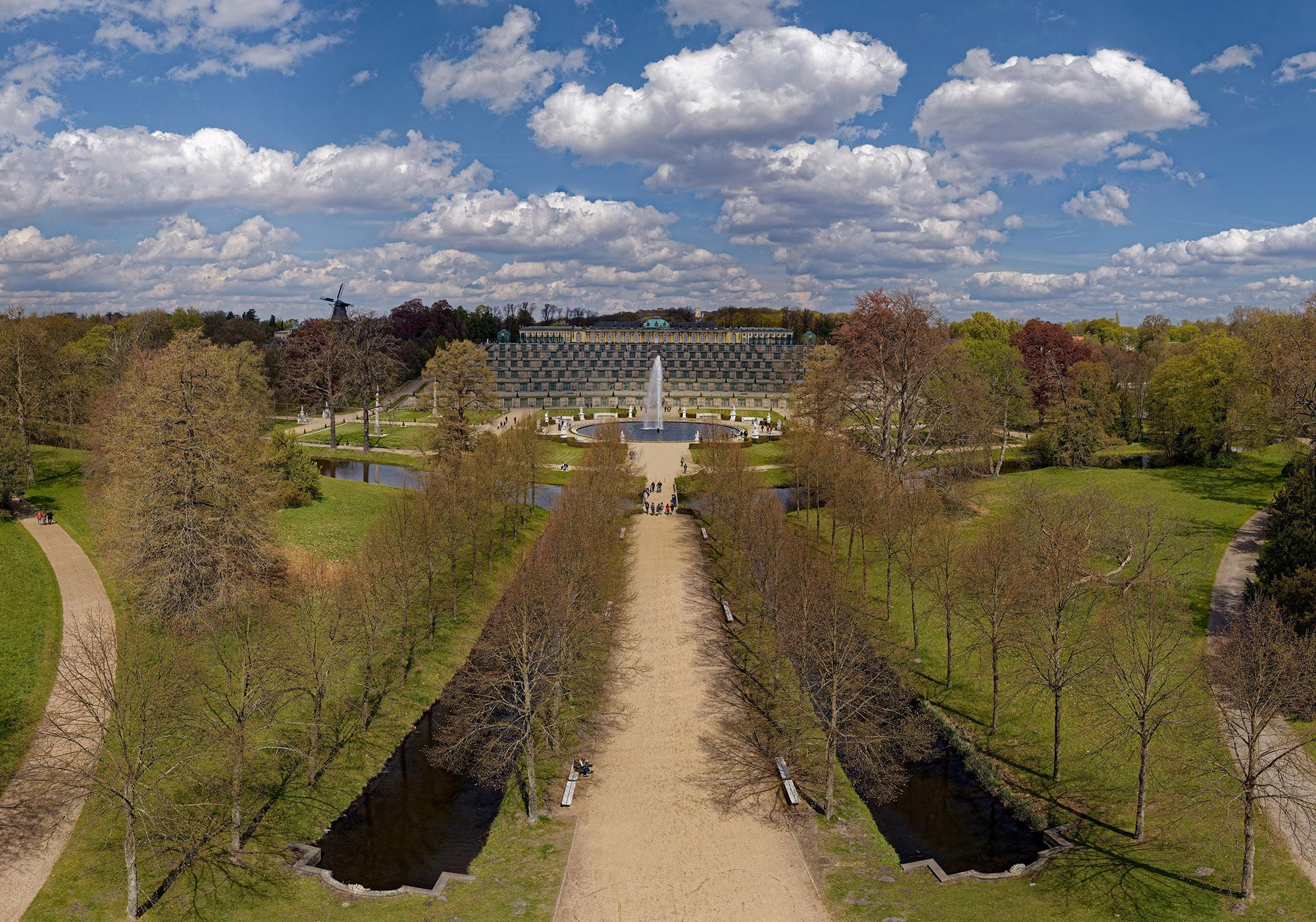 An aerial view of Sanssouci Palace and Park with the historic mill, large fountain, and famous wine terraces. – © André Stiebitz / SPSG
