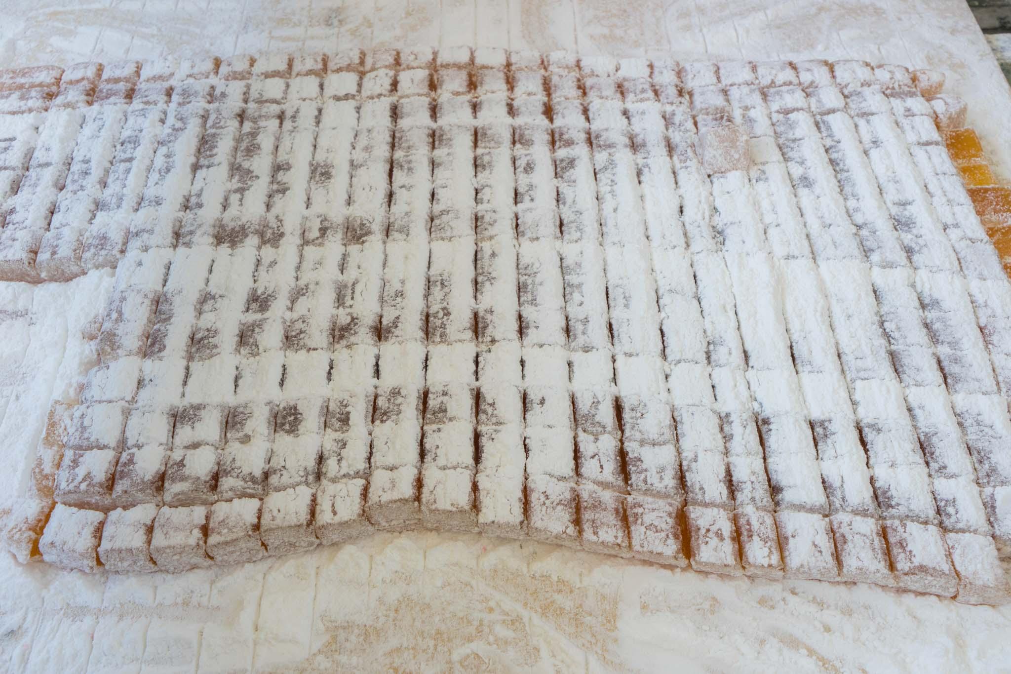 Le mélange collant est placé dans des plateaux pour qu'il refroidisse, haché en cubes, et couvert de sucre glace.  – © Michael Turtle