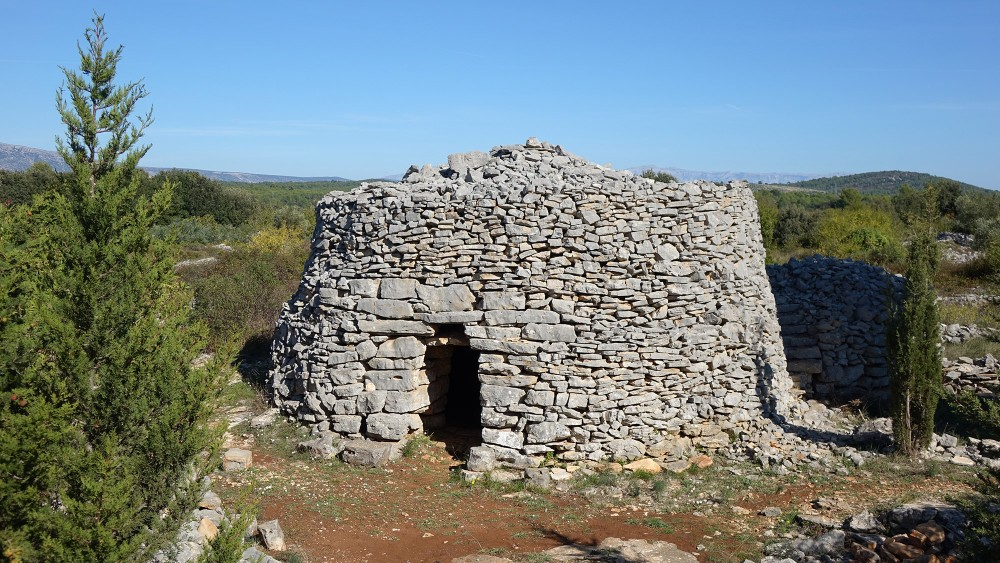 """To protect themselves from summer heat and winter rain, farmers built stone huts called """"trims"""" near their fields on the plain. – © Stari Grad Plain"""