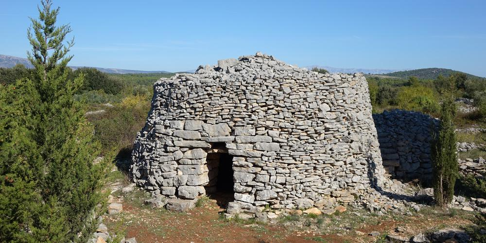 "To protect themselves from summer heat and winter rain, farmers built stone huts called ""trims"" near their fields on the plain. – © Stari Grad Plain"
