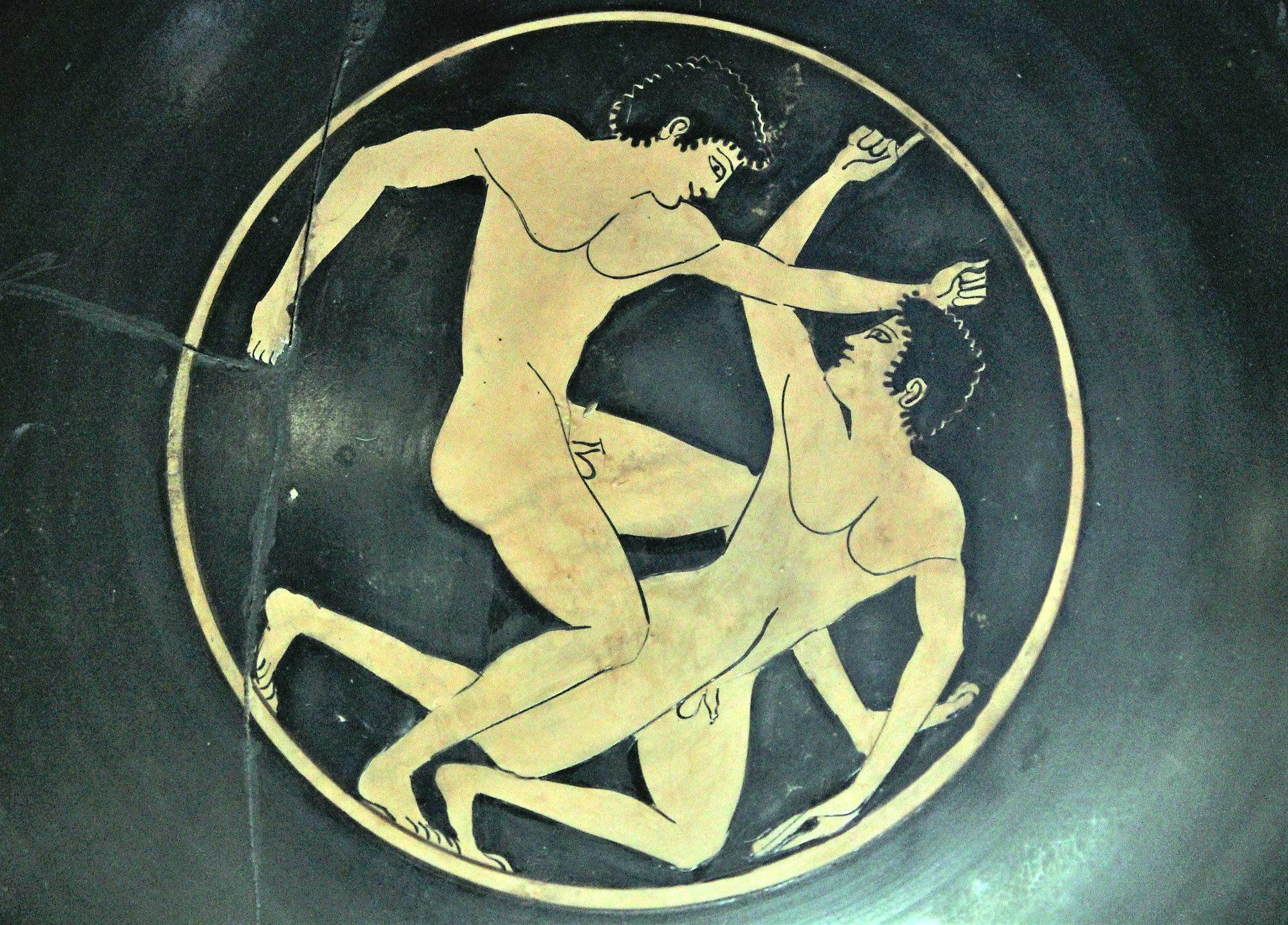 Scene from the interior of a red figure cylix (drinking cup) from the Athenian Agora—two young athletes competing in boxing. – © Hellenic Ministry of Culture and Sports / Ephorate of Antiquities of Ilia