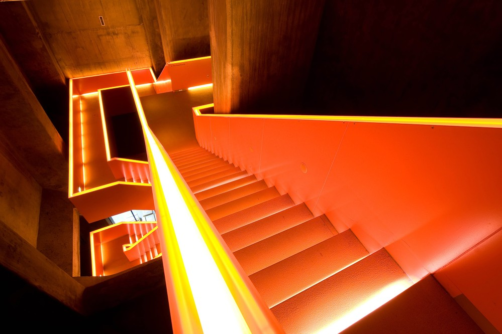 The stairwell in the coking coal bunker's nearly 20-metre-deep shaft takes visitors to the Ruhr Museum's exhibition levels. The orange colour marks a newly introduced element. – © Thomas Willemsen / Zollverein Foundation