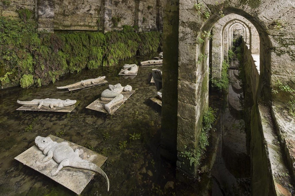 """La Fonte delle Fate, ou """"Source des Fées"""". Ces eaux sereines et sa structure immense veillent sur le sommeil d'I Dormienti, ou les Dormeurs. Cette série de sculptures en bronze a été créée par Mimmo Paladino (Arte all'Arte 1998). – © Stefano Cannas / Fondazione Sistema Toscana"""