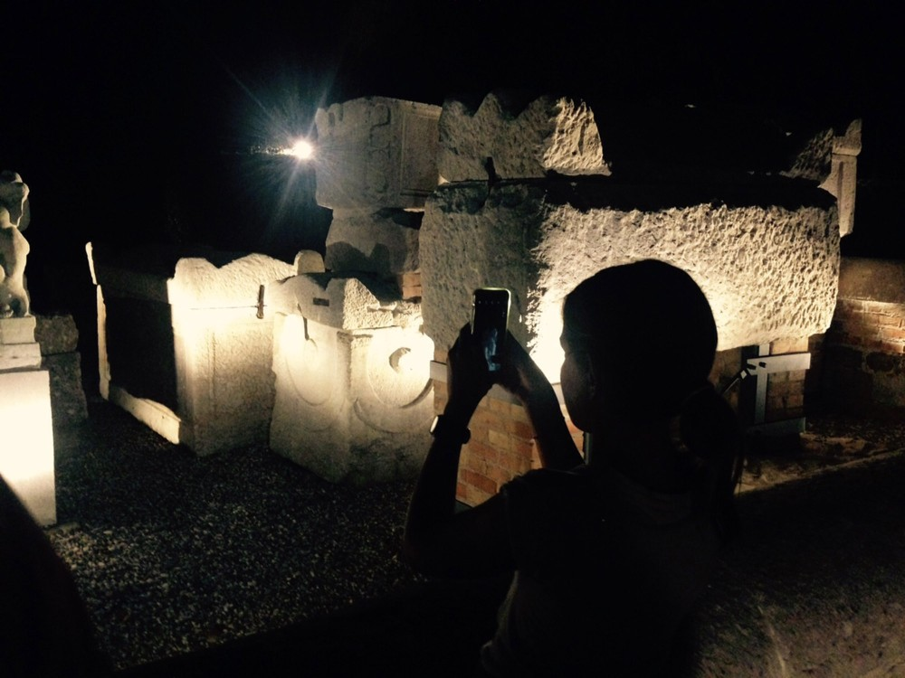 A young visitor capturing architectural details during her night visit to the necropolis. – © Erica Zanon