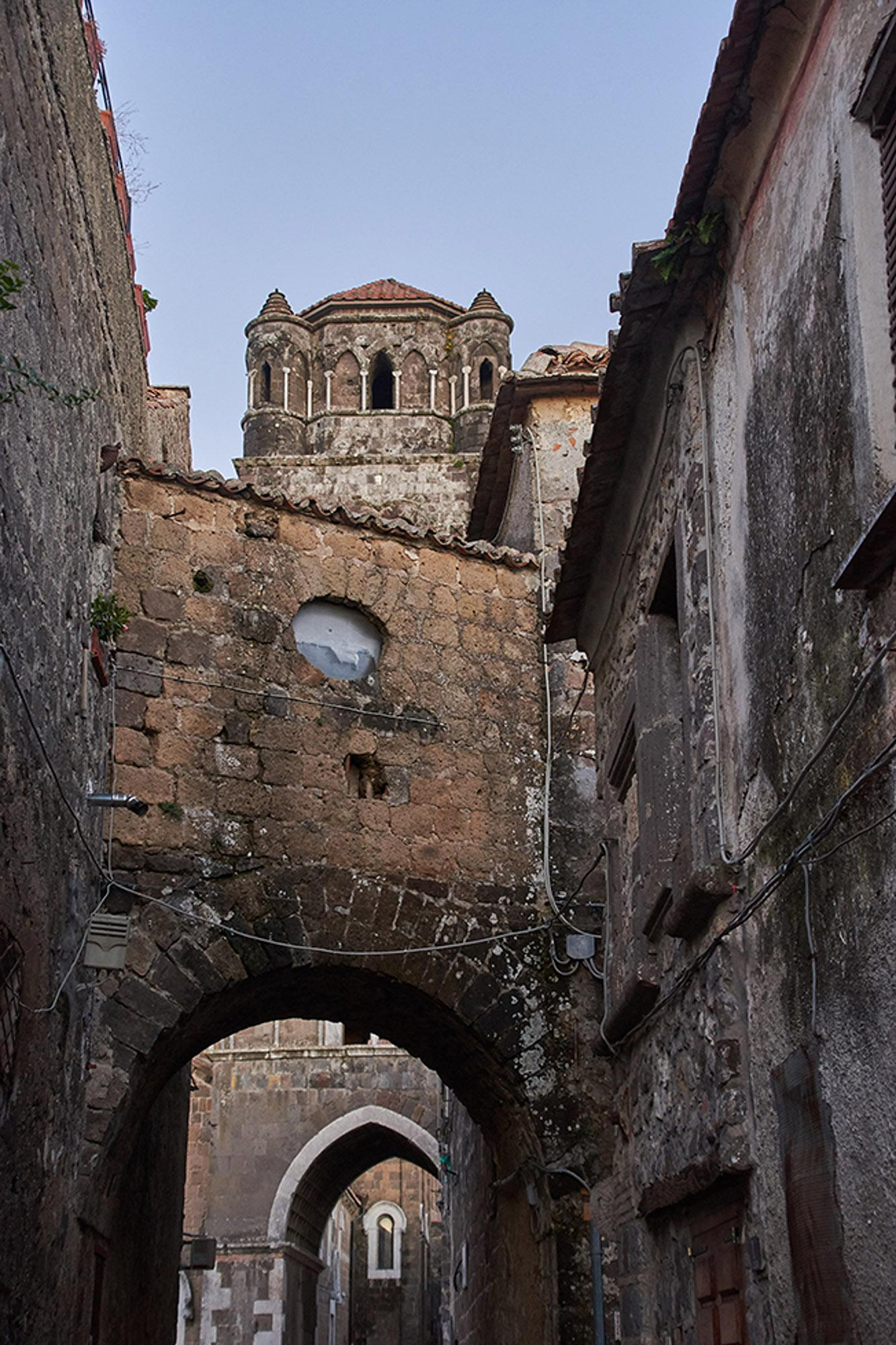 Characteristic narrow street of the ancient village of Casertavecchia, with the profile of the bell tower. – © Emma Taricco
