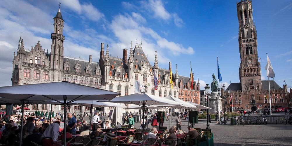 Market Square serves as the stage for a sunny day beneath the Belfry. – © Jan D'Hondt / VisitBruges