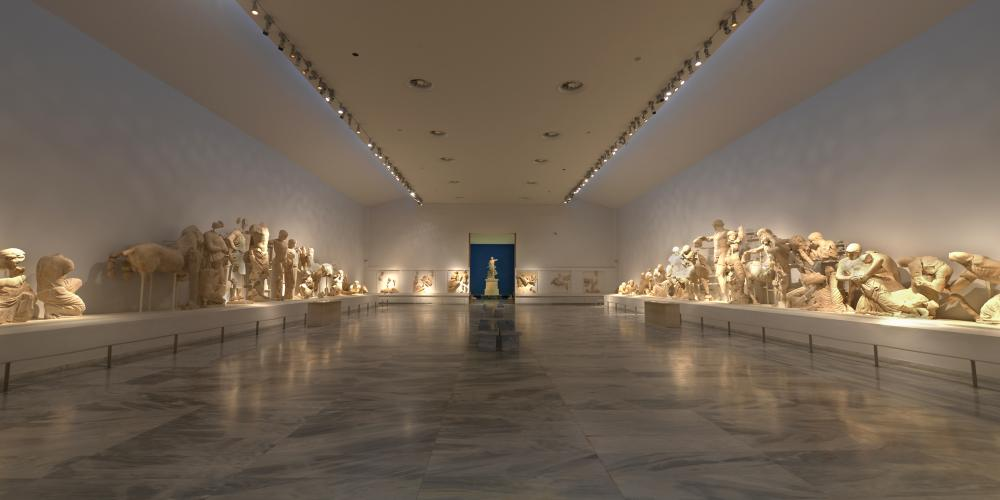 The central hall is breathtaking with the sculptural decoration of the temple of Zeus and the statue of Nike of Paionios in the background – © Hellenic Ministry of Culture and Sports / Ephorate of Antiquities of Ilia (efailias)
