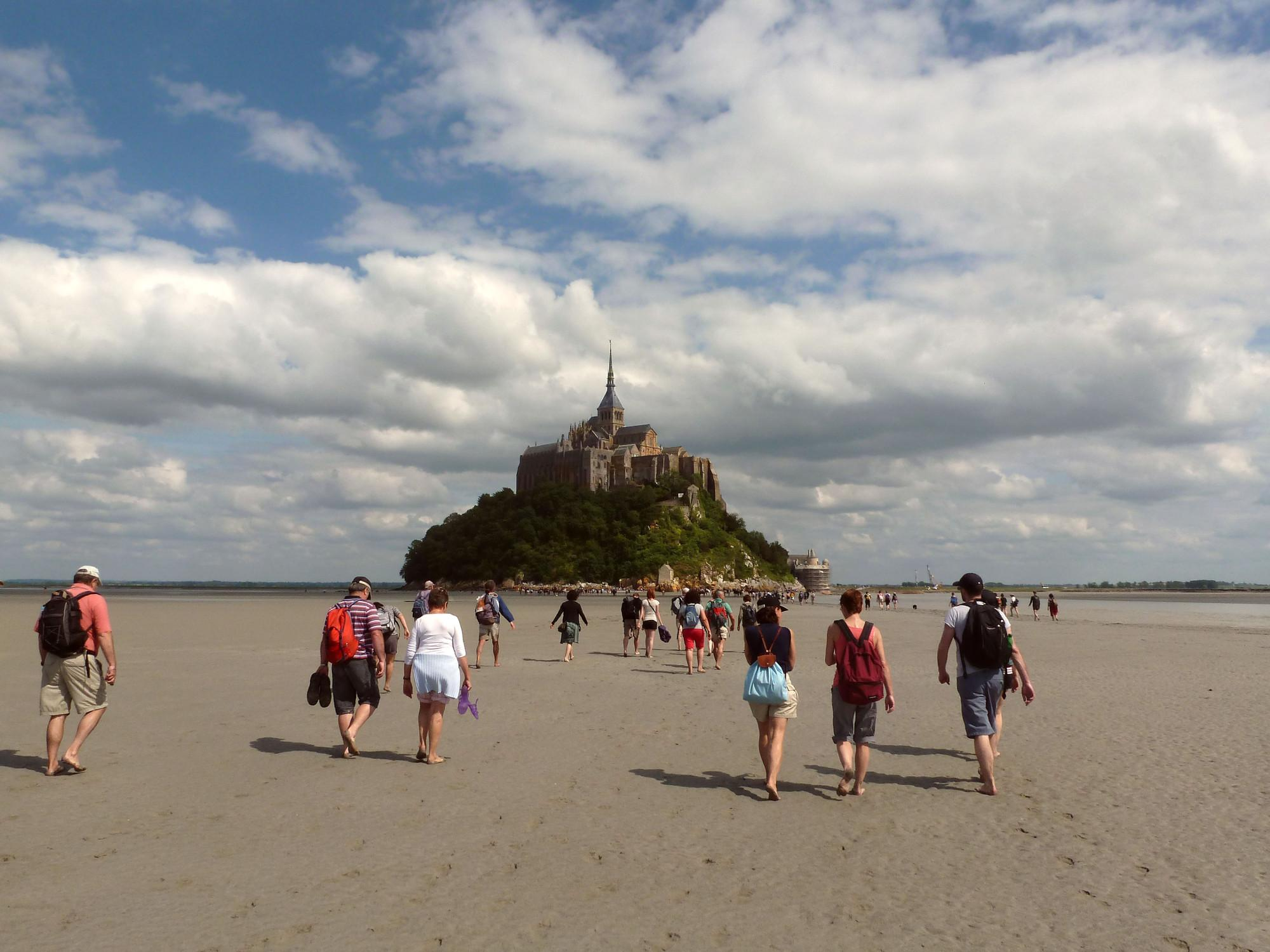 Accompanied by an experienced guide, visitors walk across the Bay of Mont-Saint-Michel, along a stretch of silvery sand, and over the meandering coastal rivers. – © K. Riley / CRT Normandie
