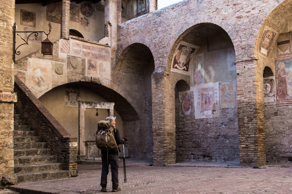 A pilgrim arriving in the court of the Public Hall in San Gimignano from Gambassi Terme. – © Andrea Miserocchi / talian Stories