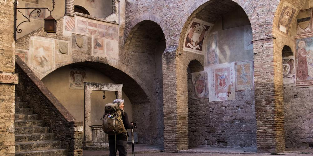 A pilgrim arriving in the court of the Public Hall in San Gimignano from Gambassi Terme. – © Andrea Miserocchi / Italian Stories
