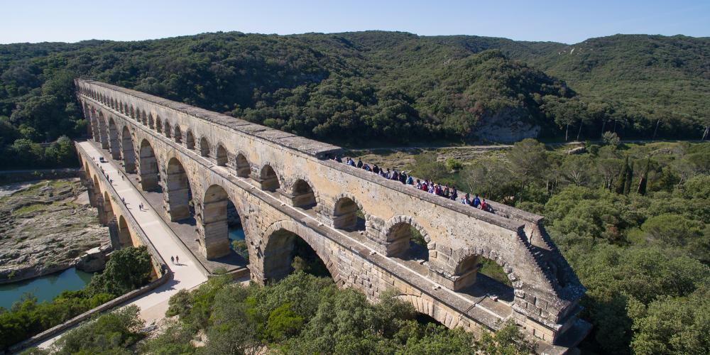 游人在导游的带领下探究罗马人2000年前修建的最高的水道桥。 – © François Allaire