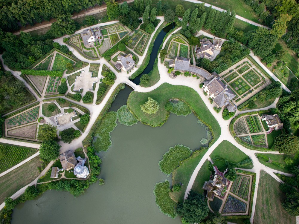 """Following the European taste for the """"fermes ornées,"""" Marie-Antoinette tasked Richard Mique with extending the gardens to the north and building a whole model village around an artificial lake. Combining various influences from rural architecture, the queen enjoyed an etiquette-free life with her close friends in her cozy cottage. – © Toucan Wings"""