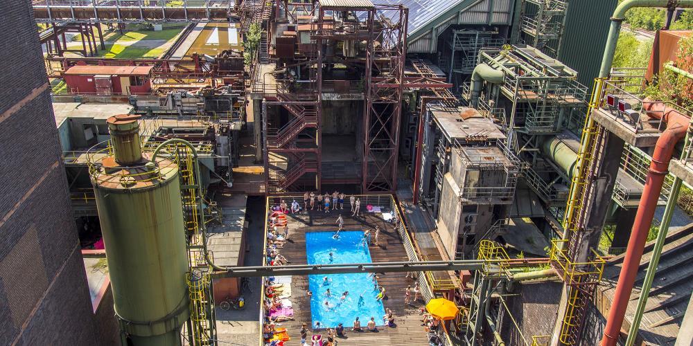 Vue aérienne de la piscine avec vue sur l'usine de mélange à gauche et la longue batterie de fours à coke avec un système d'énergie solaire. – © Jochen Tack / Zollverein Foundation
