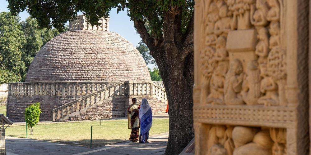 Stupa number 3 on the main terrace at Sanchi, as seen through the carved northern gateway of the Great Stupa. – © Michael Turtle