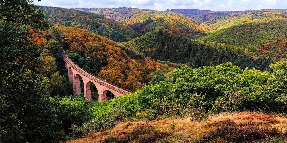 The epic Boppard-Buchholz-Emmelshausen mountain rail traverses the Boppard Forest. Pictured: the railway viaduct near Boppard at Moselle River. – © rphstock / Shutterstock