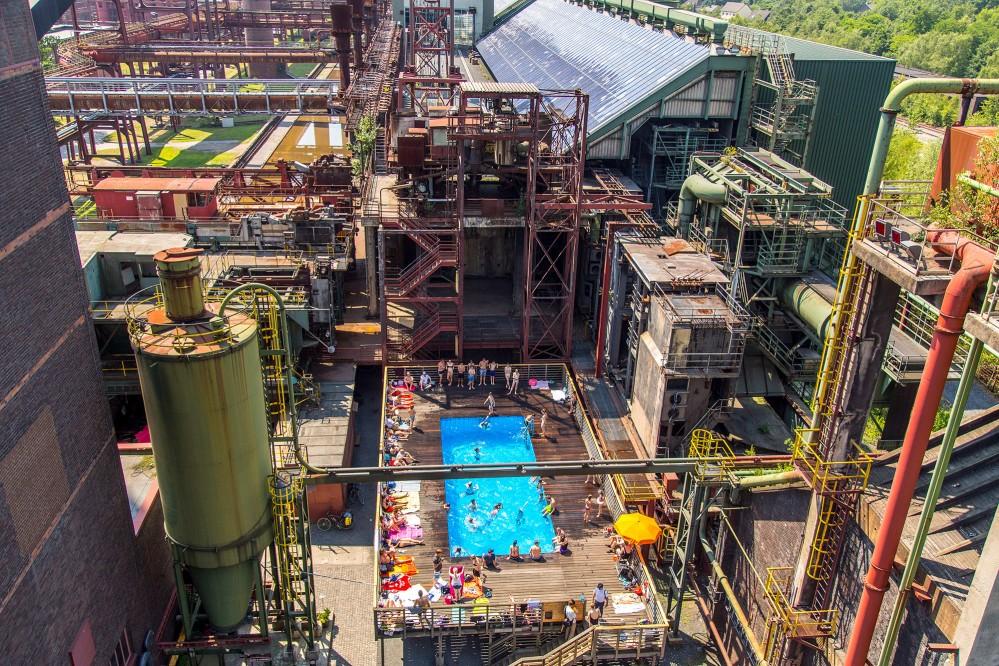 Une piscine bleu clair au milieu de la cokerie de Zollverein : Pendant les vacances d'été en Rhénanie-du-Nord-Westphalie, les visiteurs de Zollverein peuvent se rafraîchir et se détendre dans cette piscine. – © Jochen Tack / Zollverein Foundation