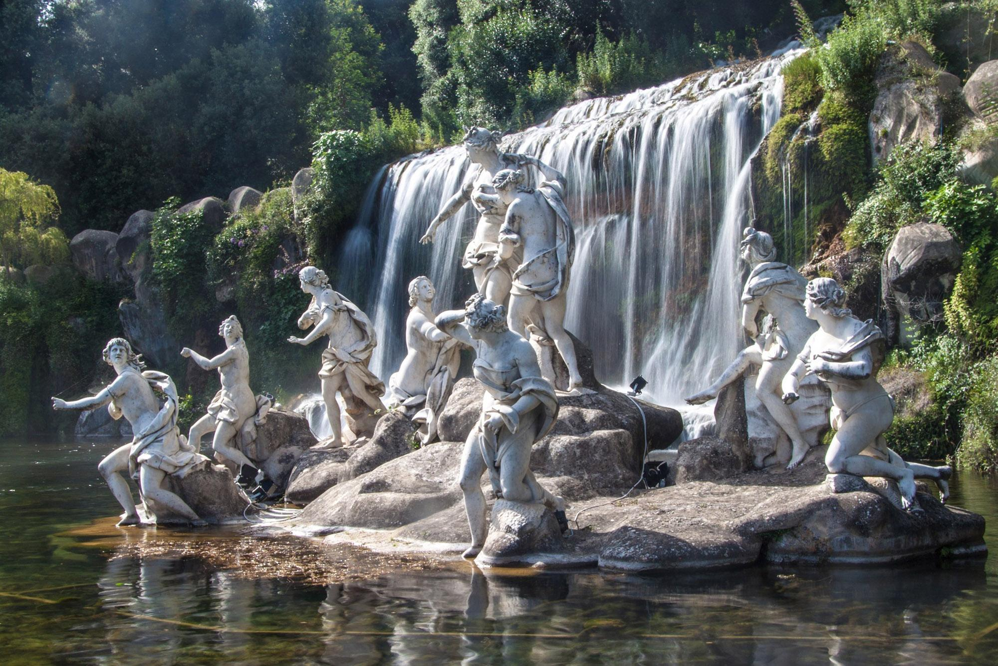 Le parc royal fait partie intégrante du domaine et inclut le jardin, qui s'étend sur 120 hectares et où les visiteurs peuvent voir cette cascade et ce groupe de statue. – © Matyas Rehak / Shutterstock