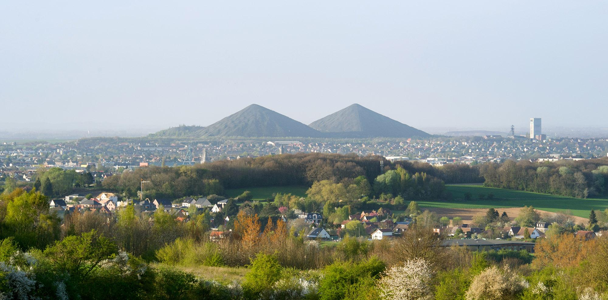"Contemplate three hundred years of history from the top of the spoil heaps by climbing the sensational ""Pyramids"" of the North. Pictured: a view of the twin slag heaps in Loos-en-Gohelle from the Canadian National Vimy Memorial. – © Jean-Michel André"