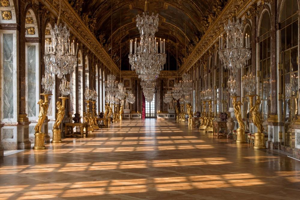 La galerie des Glaces, salle la plus célèbre du palais, fut construite par Jules Hardouin-Mansart en 1678 et son plafond voûté fut peint par Charles Le Brun entre 1681 et 1684. A cette époque, les miroirs valaient extrêmement chers et les dix-sept arches reflétaient le pouvoir et la richesse de la France. – © Thomas Garnier