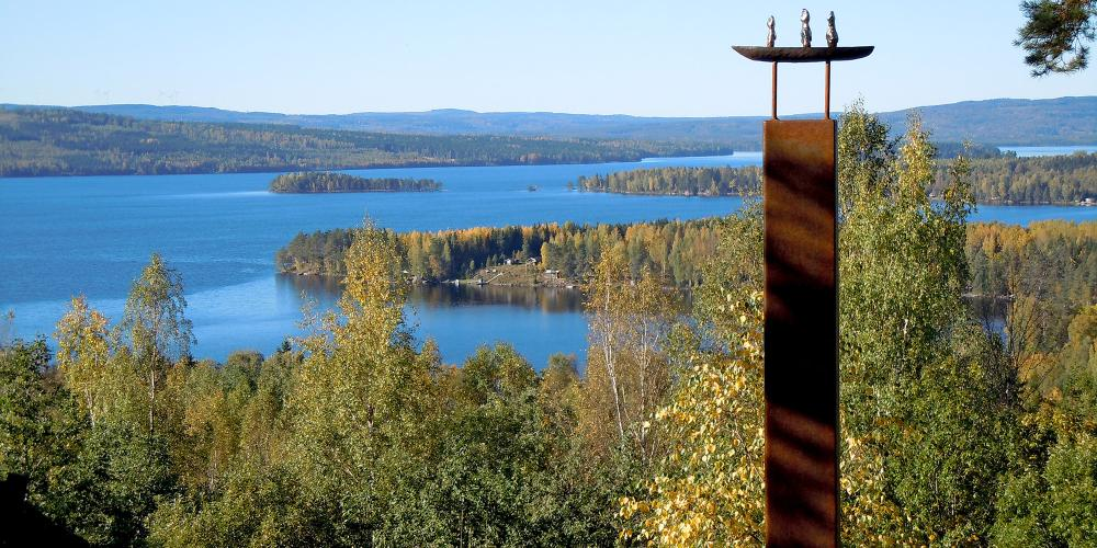 A shot from the Lekomberg mine outside Ludvika, shows the forest and river, and a sculpture made from iron and steel. – © Ekomuseum Bergslagen