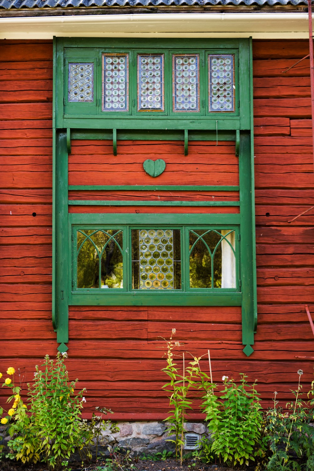 The home of Carl Larson is equally beautiful on the outside. Leaded-glass windows framed by green decorations. The heart is a recurring symbol all over the house. – © Carl Larsson-gården