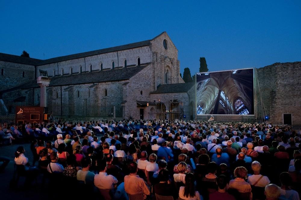Le Festival du film d'Aquilée a lieu fin juillet et est aprécié par les visiteurs de tous âges. La Piazza Capitolo et la basilique prennent une perspective toute nouvelle - et morderne. – © Gianluca Baronchelli