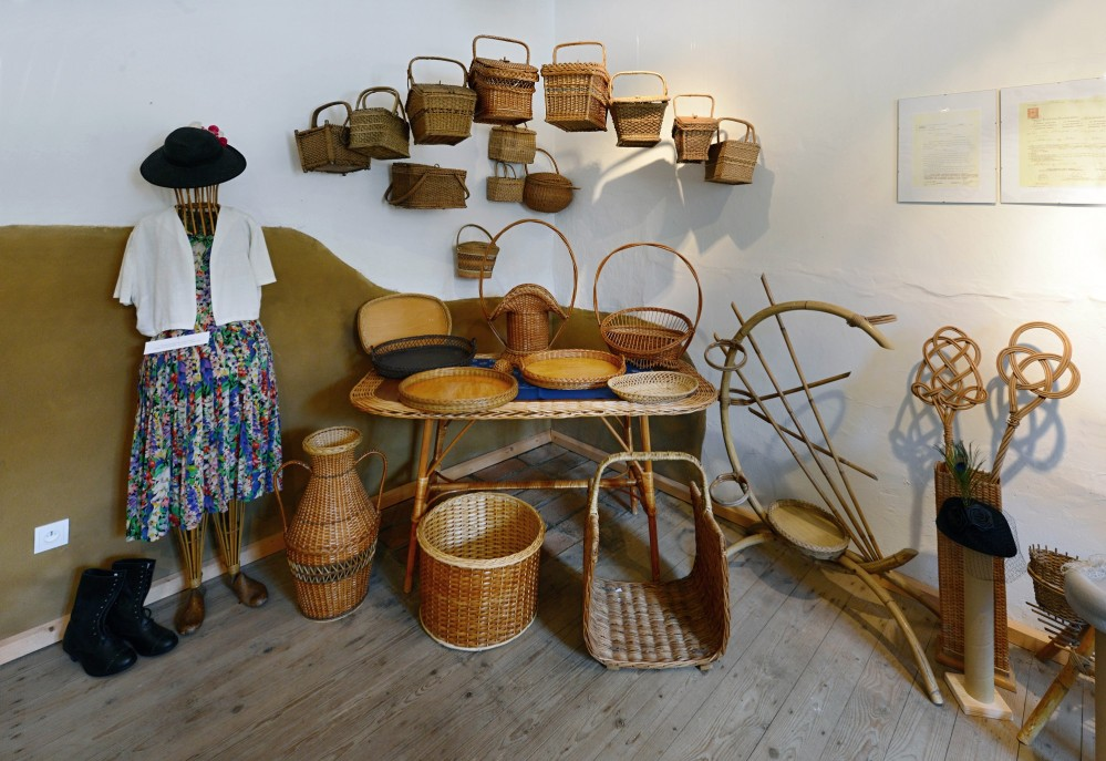 The interior of the museum - a figure from an exhibition on hats held in 2016. There are travel and market baskets, bowls, and bakery equipment.